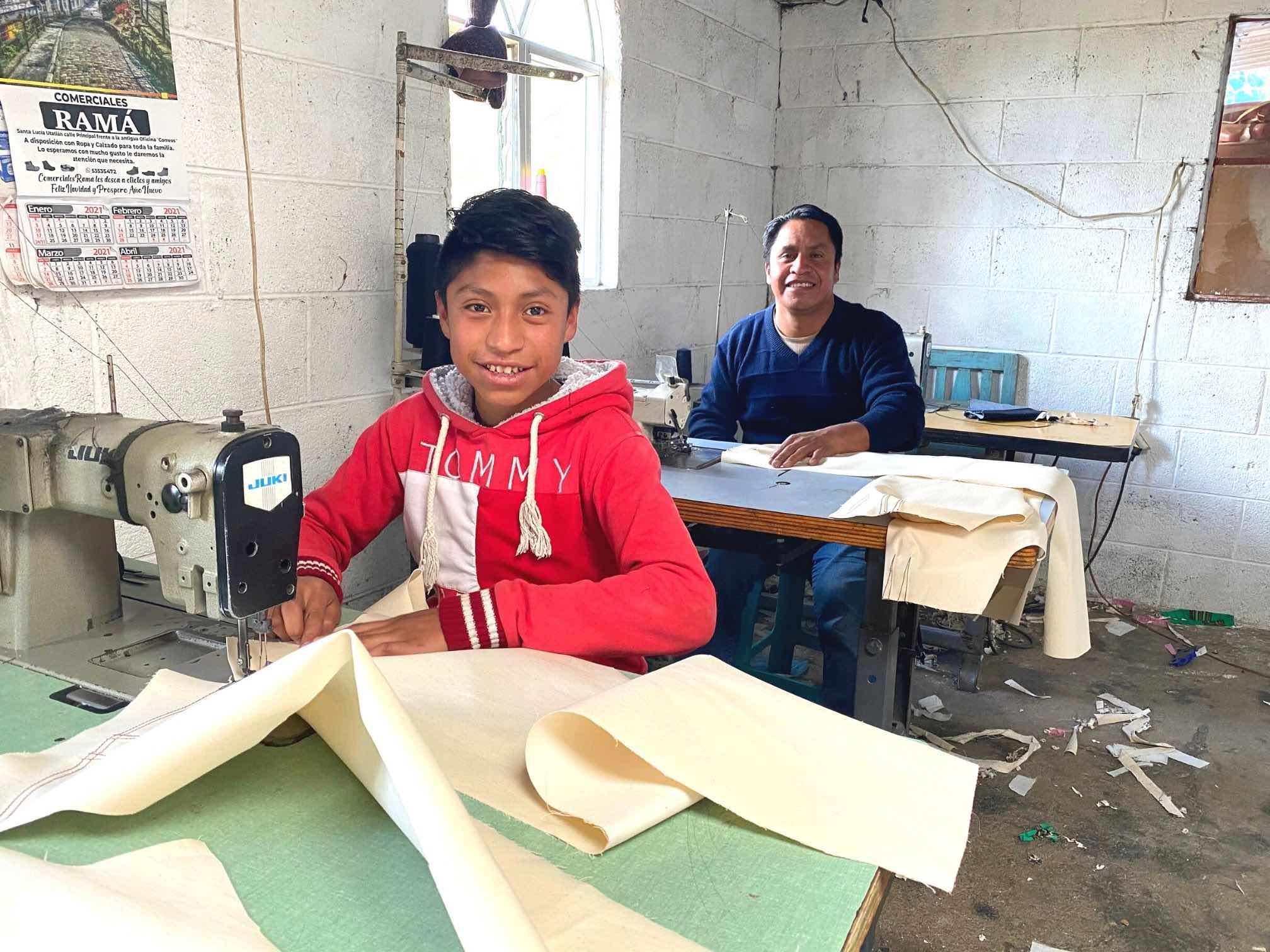 Guatemalan boy uses sewing machine in workshop