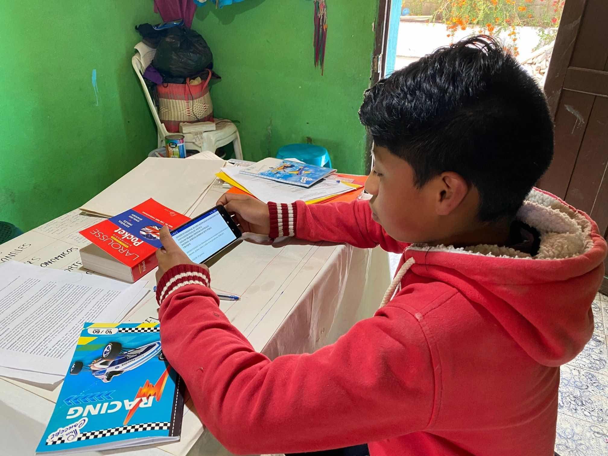Guatemalan boy using cell phone to do his homework