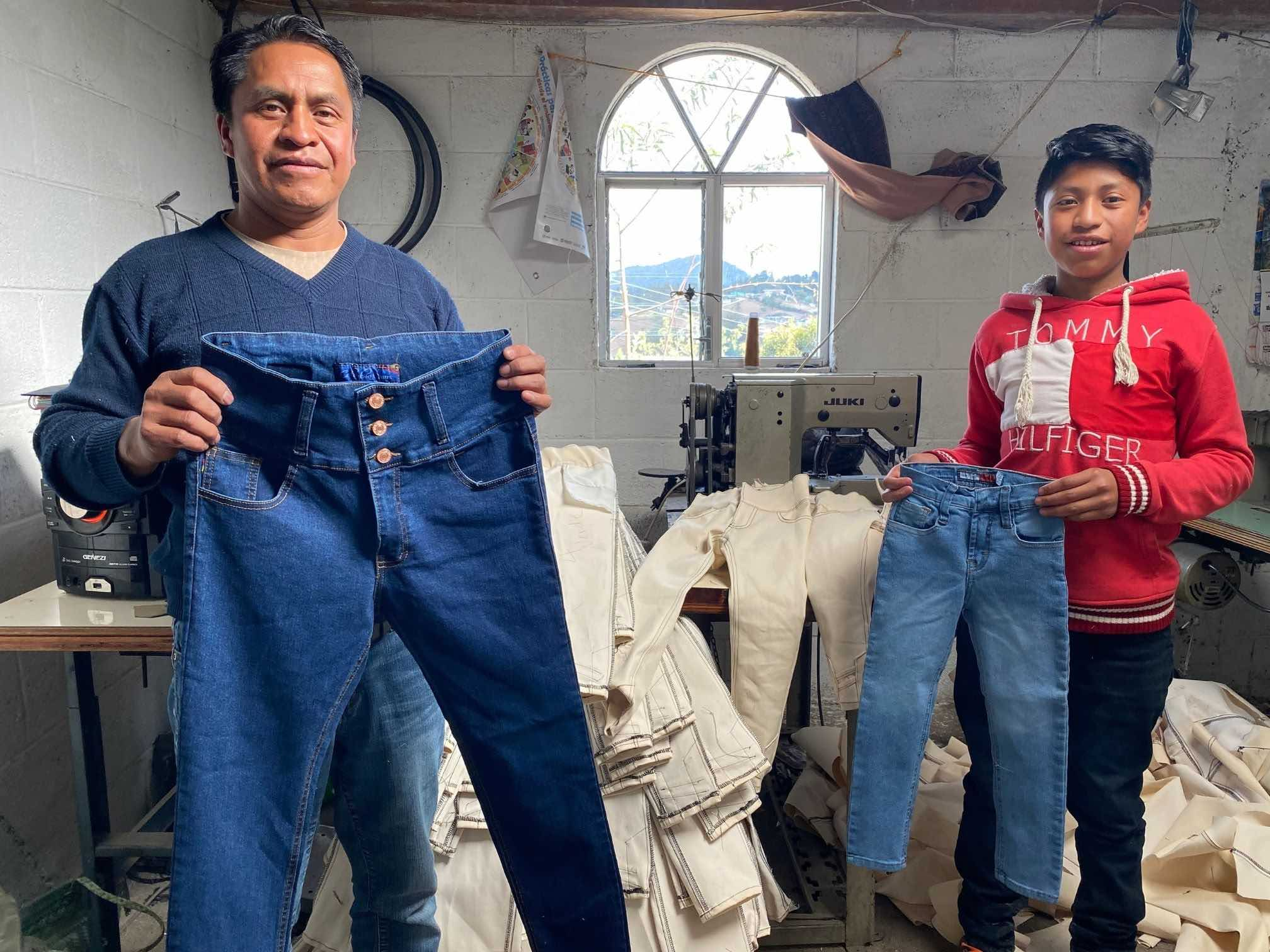 Father and son holding up pair of pants