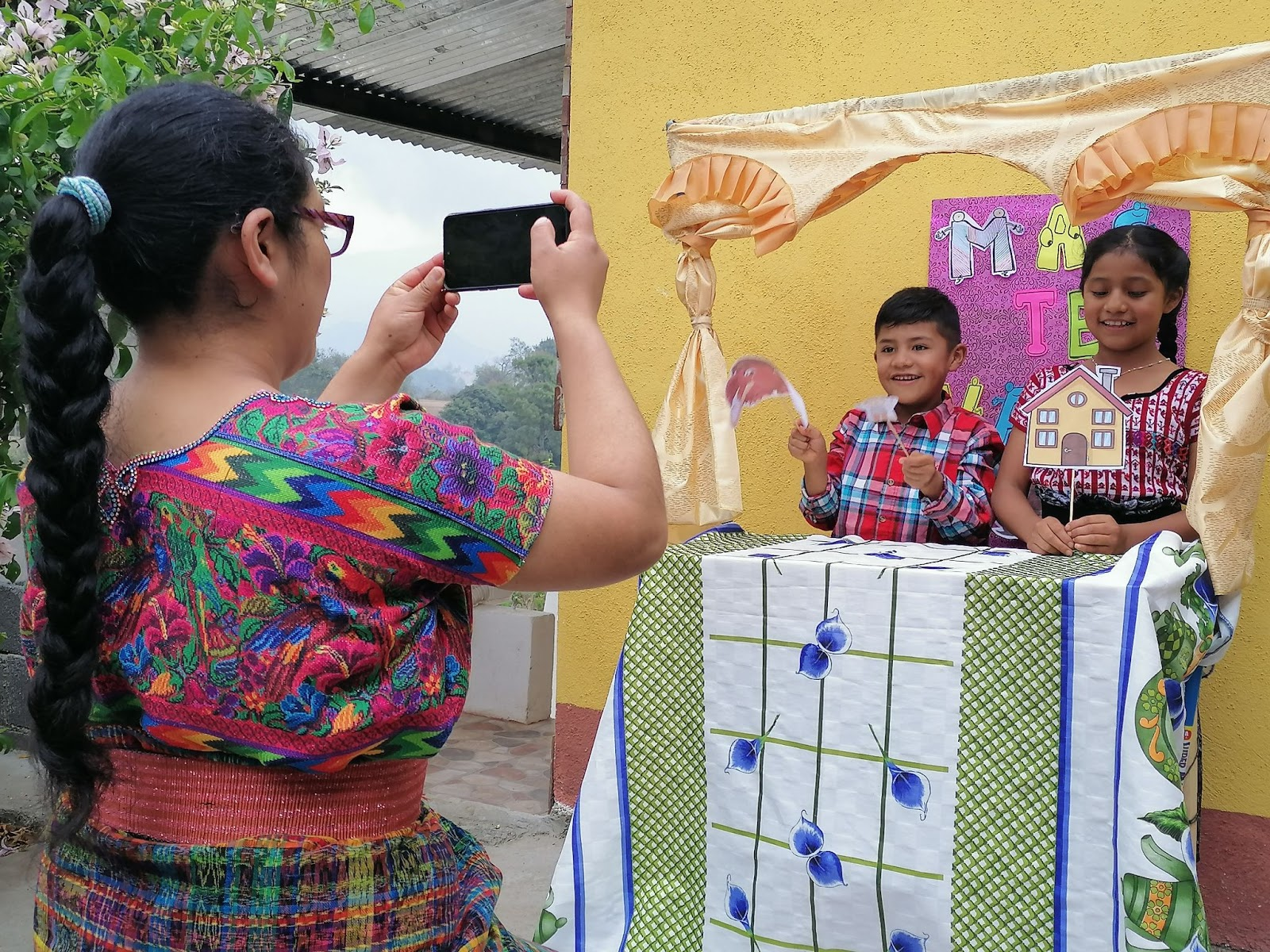 Children performing puppet show while mother films