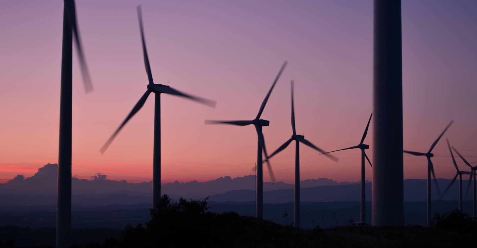 Ein Foto von Windrädern vor dem Sonnenuntergang
