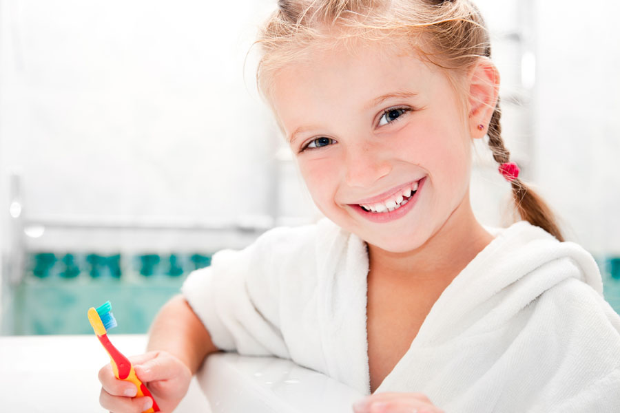 Young girl holding toothbrush and smiling