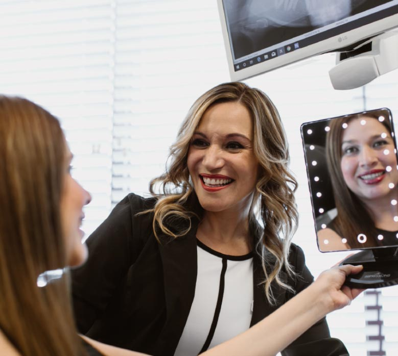 Photo of Dr. Paola with a patient looking into a mirror
