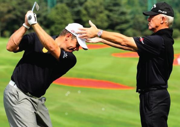 Golf instructor keeping head of a player still mid-swing