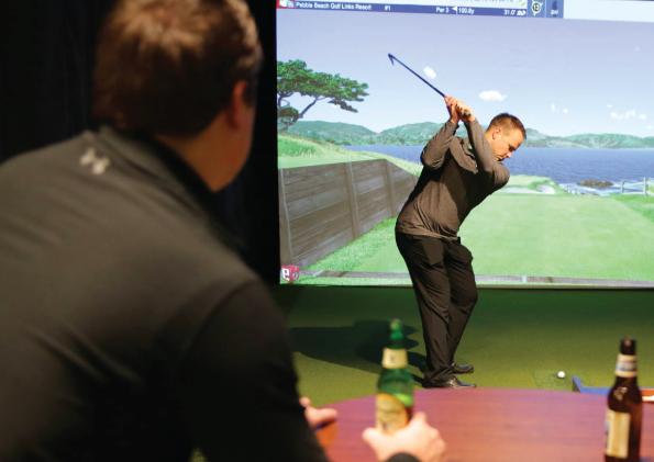 Man swinging at a golf simulator