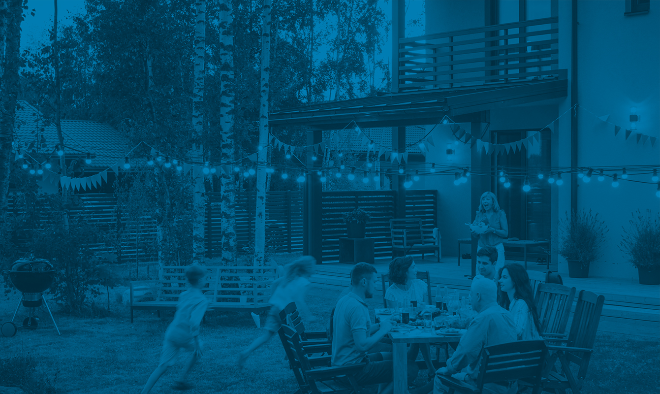 Blue overlay showing family celebrating picnic outside – Hoiberg
