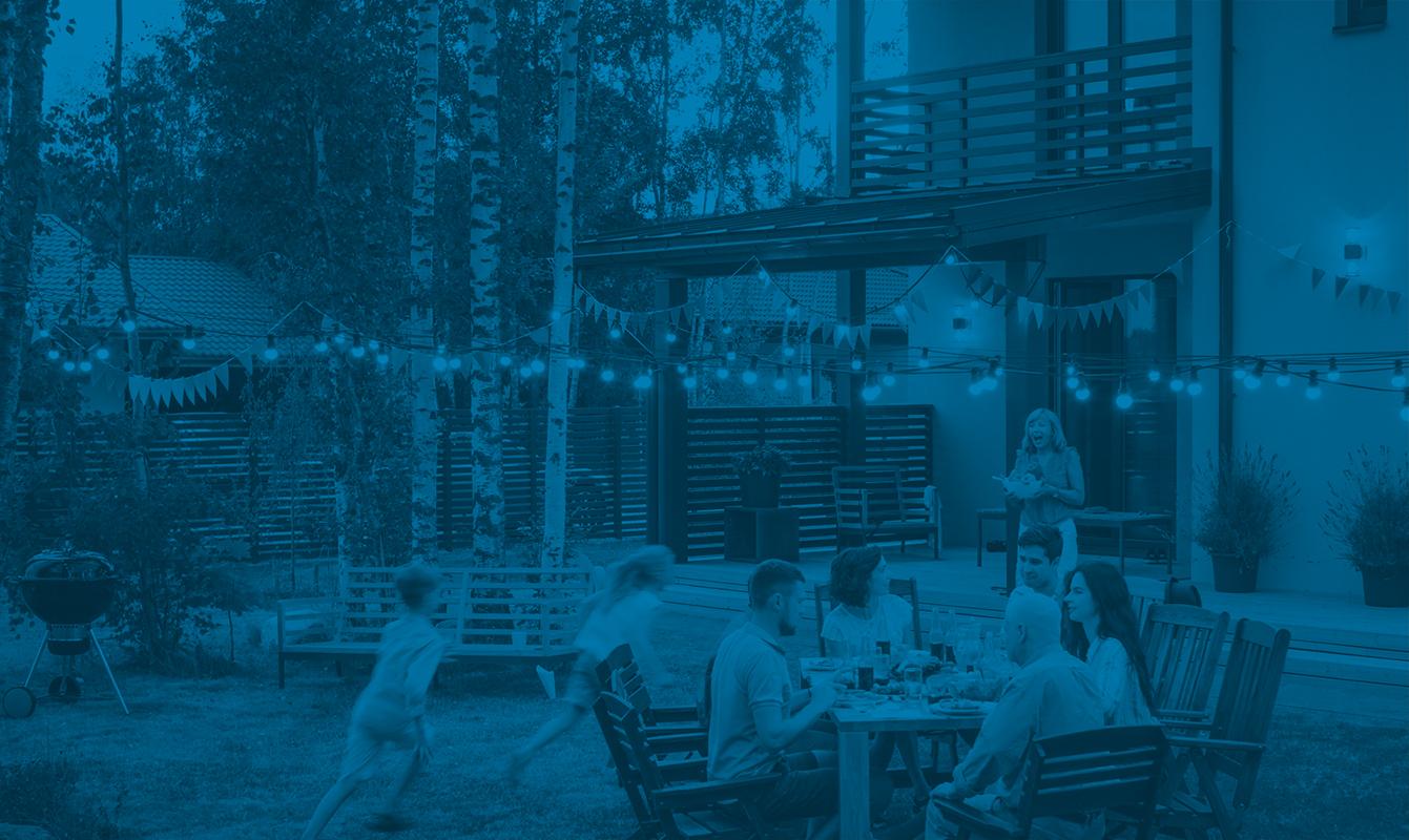 Blue overlay showing family celebrating picnic outside – Hoiberg