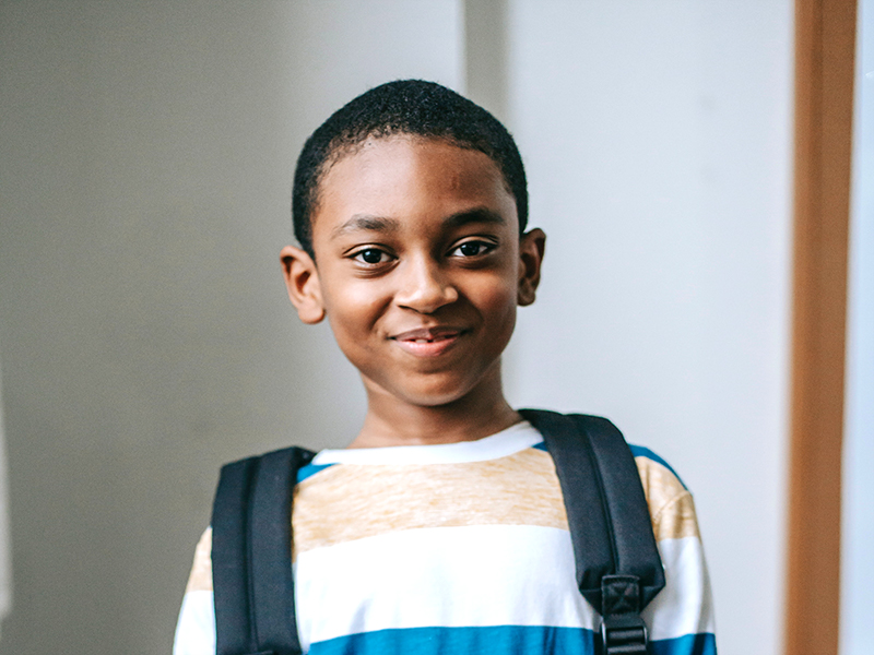Child smiling at camera wearing a school backpack