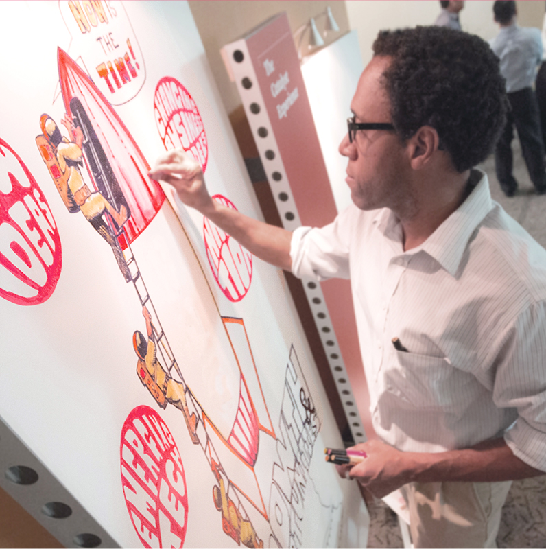Man illustrating a rocket ship wearing a button down shirt holding a red marker
