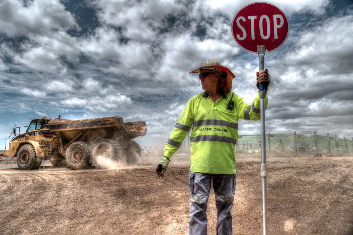 Traffic controller on construction site captured by professional photographer employed by Rapax Construction Photography