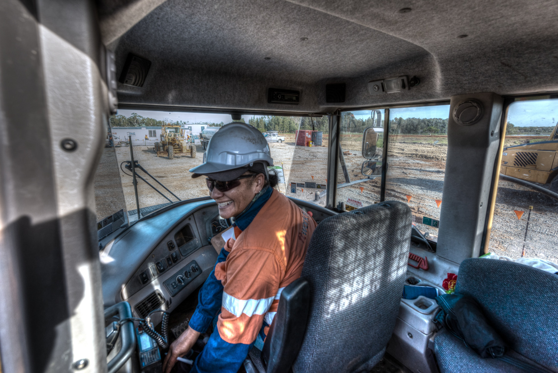 The smiling operator of a large dump truck captured by a professional photographer skilled in construction photogrpahy