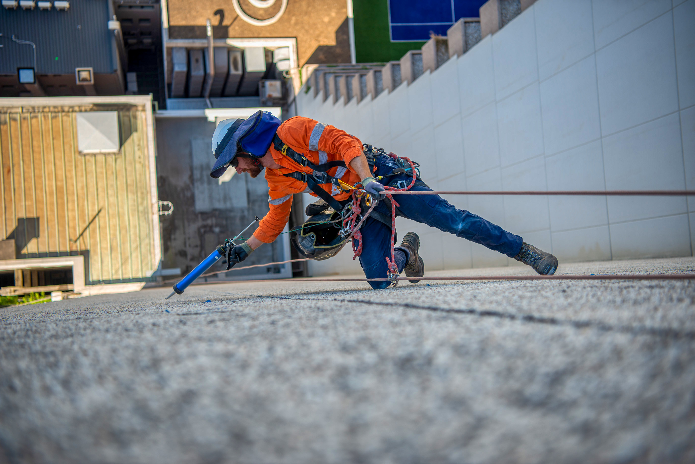 Reaching to repair the side of a high rise building and captured by Rapax Construction Photography