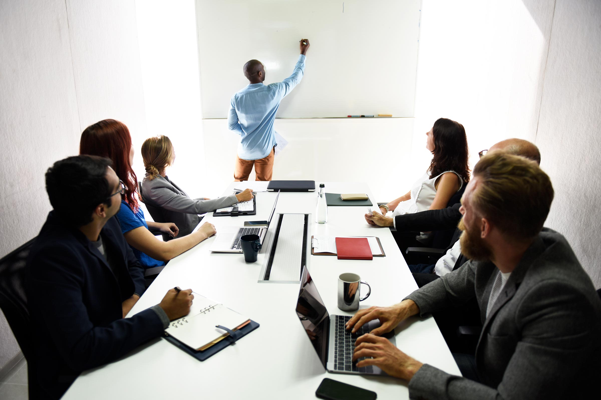 Man training a group of employees English in a classroom