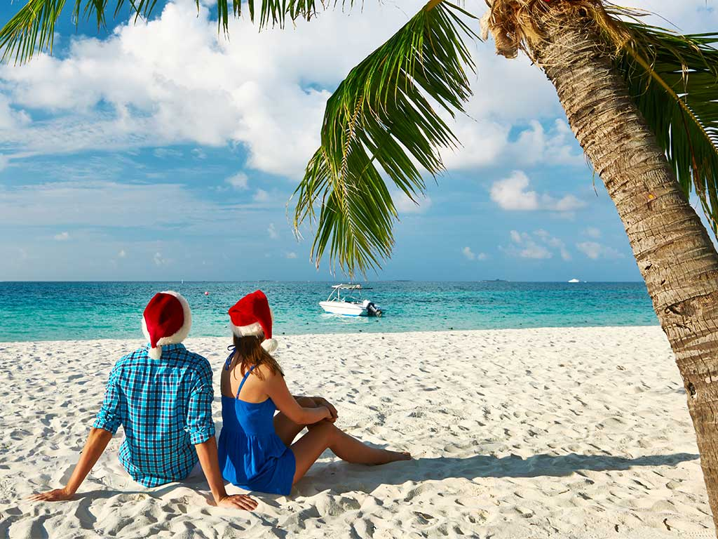 couple wearing christmas hats sitting on a tropic beach under a palm tree - Cheap Christmas Flights