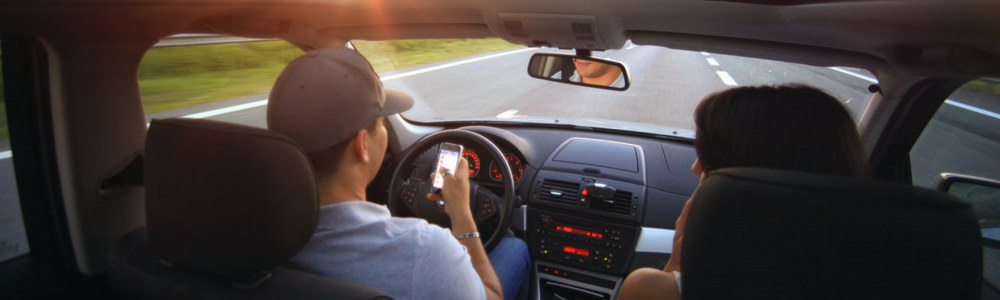 Young driver using mobile phone while driving