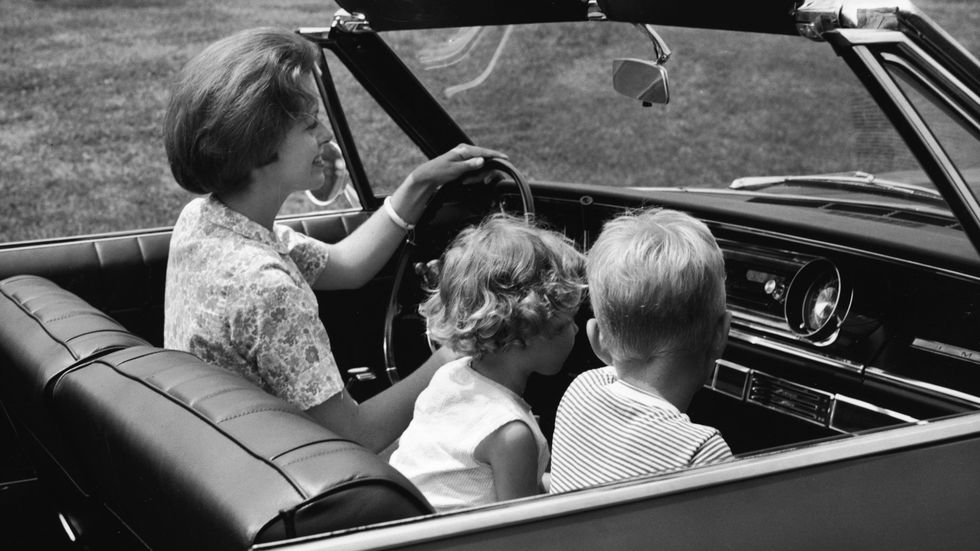 Kids sitting in front seat of car