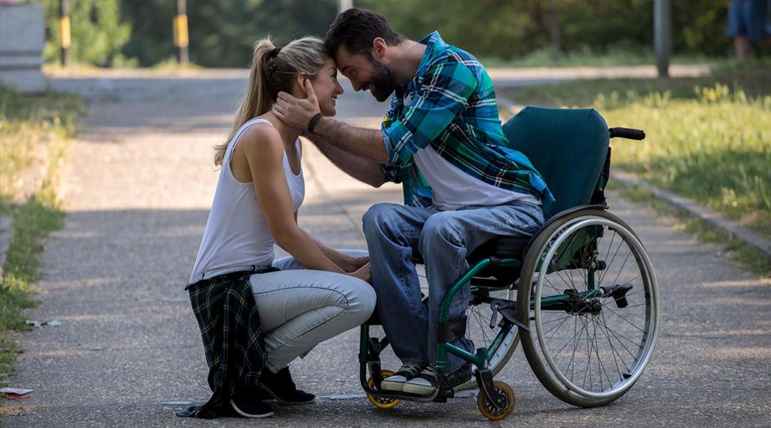 Man in wheelchair hugs his girlfriend
