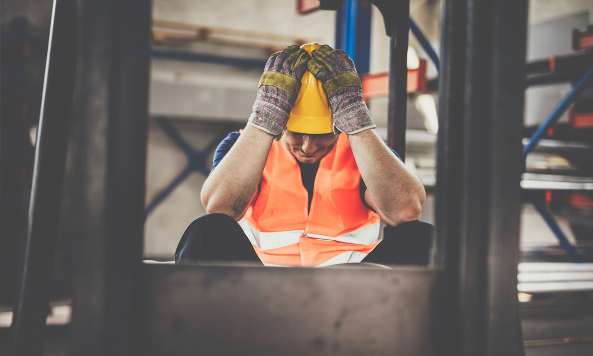 Stressed out worker in hard hat with hands on head