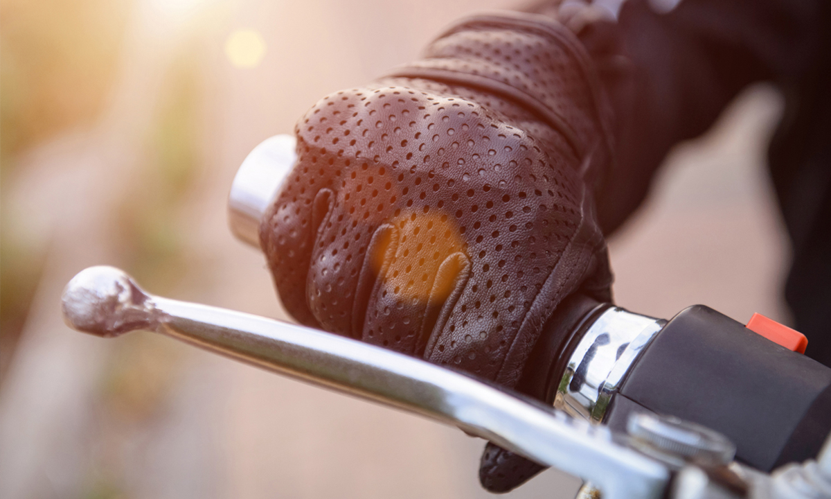 Holding onto motorcycle handlebars with gloves