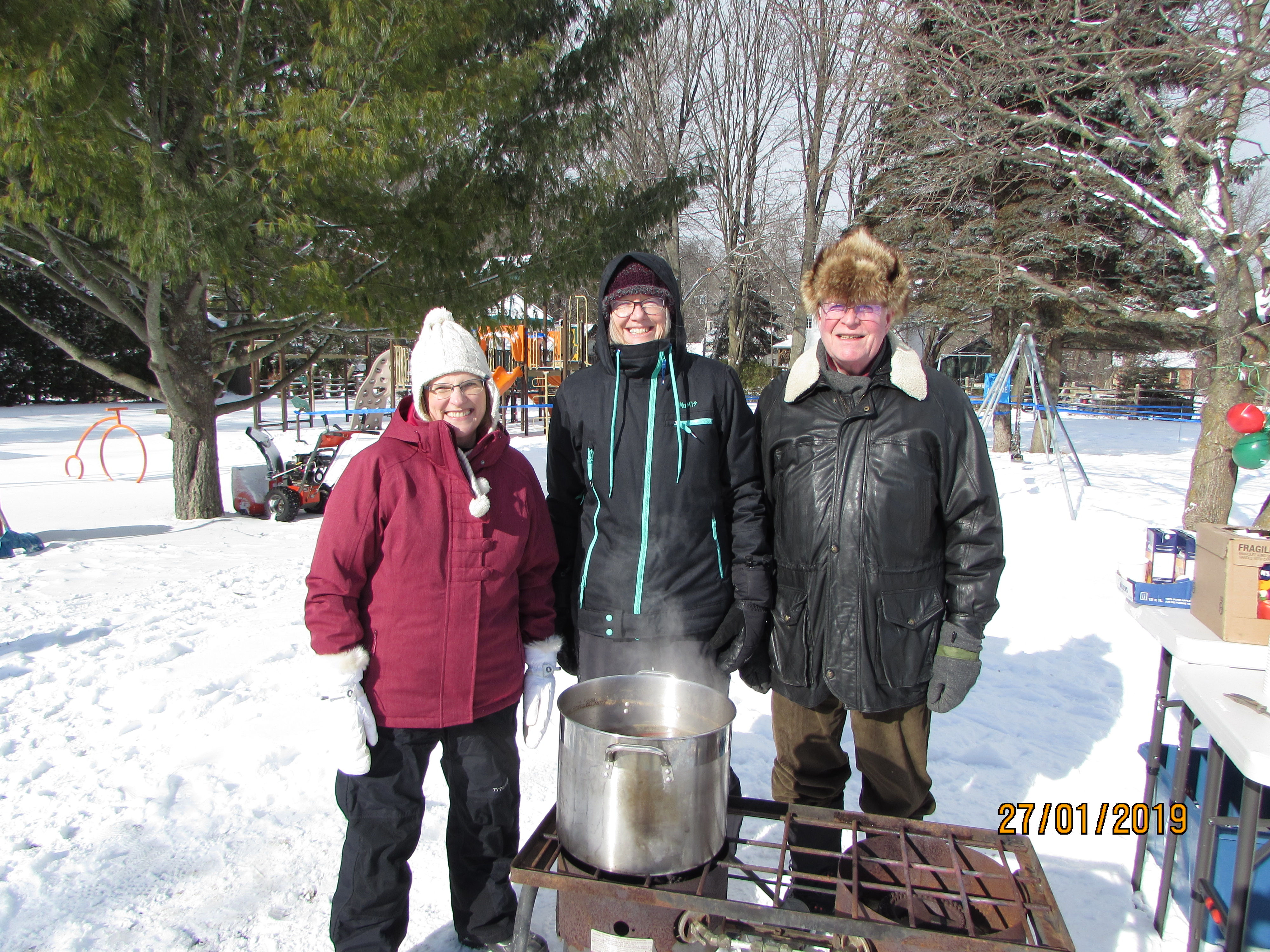 Group of 3 around hot apple cider pot