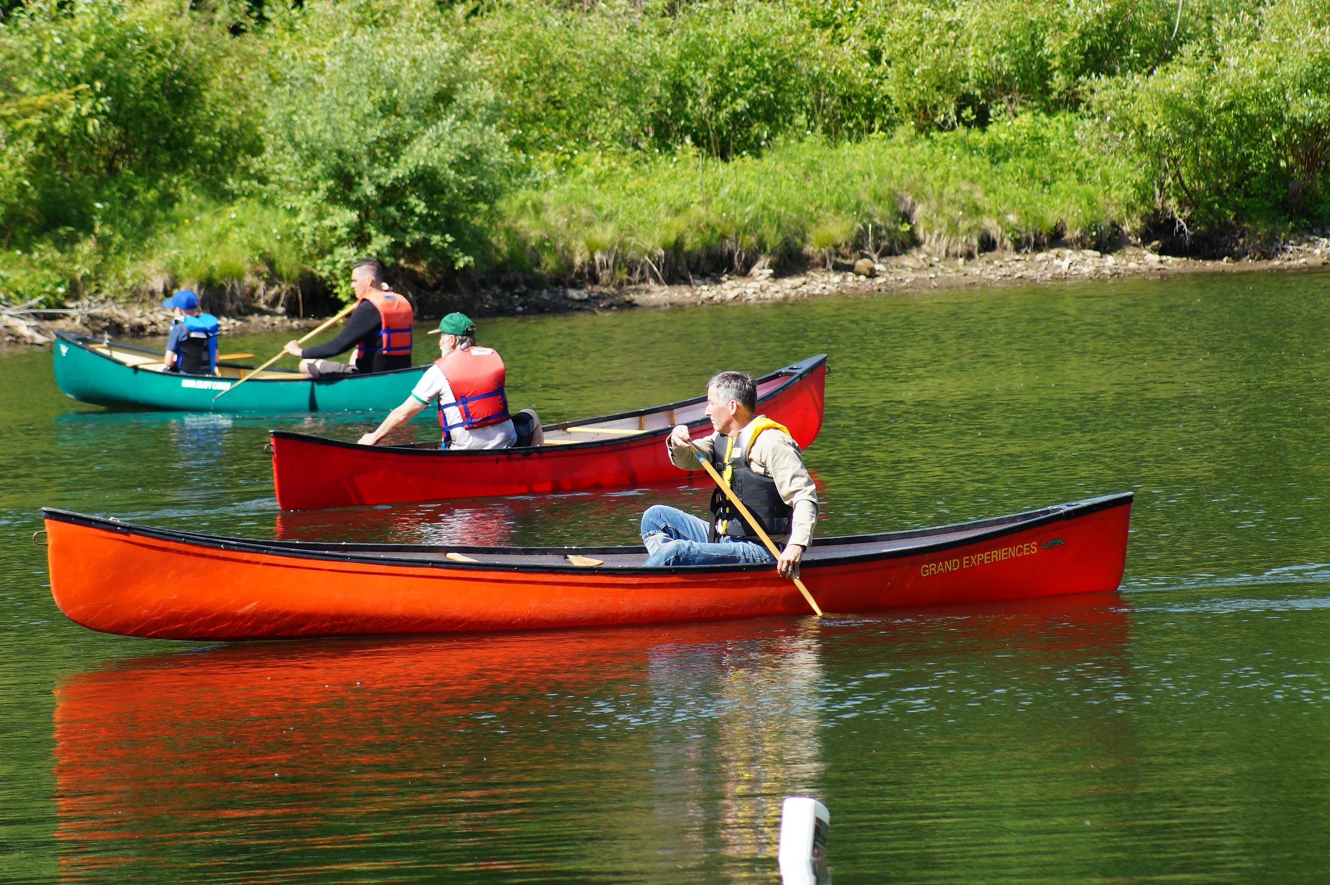 One man canoeing past a couple other canoe participants