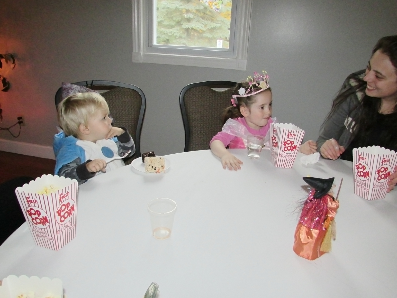 Two children and an adult enjoying popcorn and rice crispy squares at a table