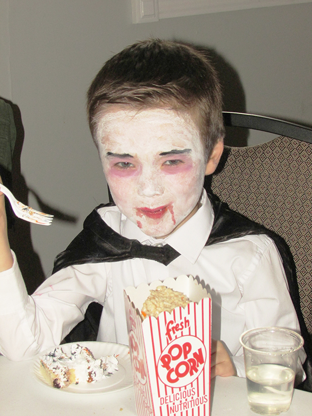 Child in a vampire costume eating cake