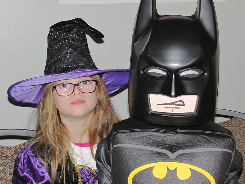 Child in a witch's costume and child in a Lego Batman costume