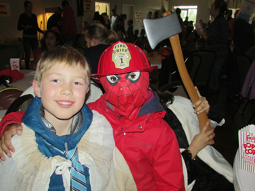 Two Children: One dressed as a Spiderman fire chief