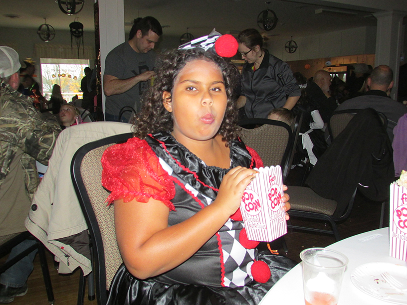 Child in a Halloween costume eating popcorn