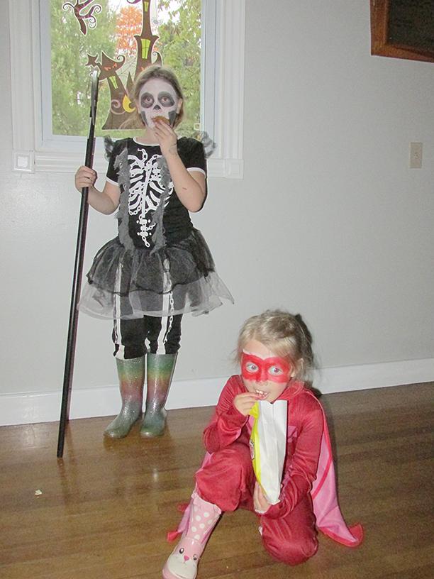 Two children posing in Halloween costumes