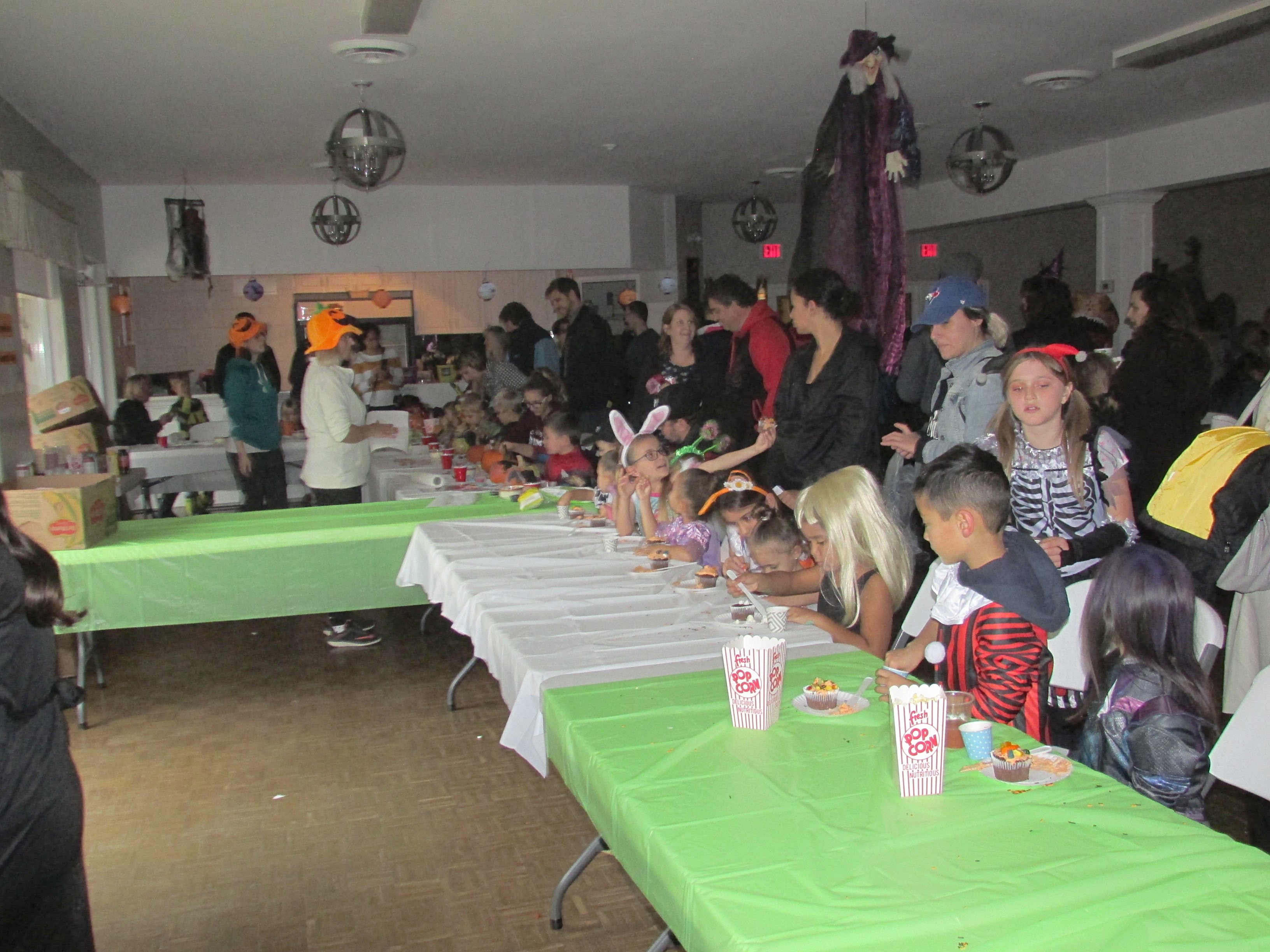 Children in Halloween costumes gathered around a table