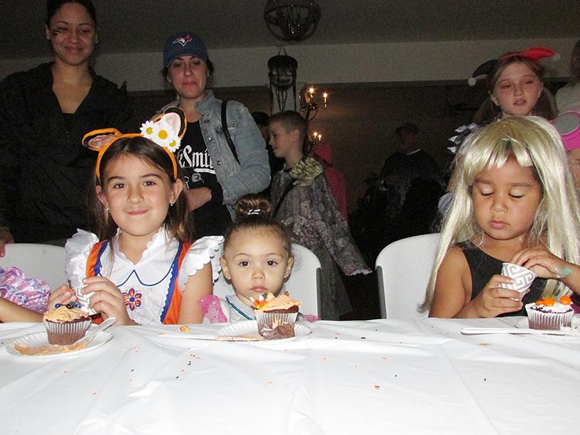 3 children in Halloween costumes eating cupcakes