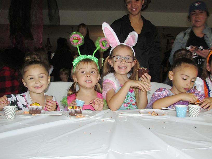 Four children in Halloween costumes