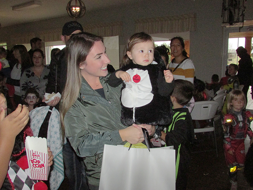 Woman holding child in a Halloween costume