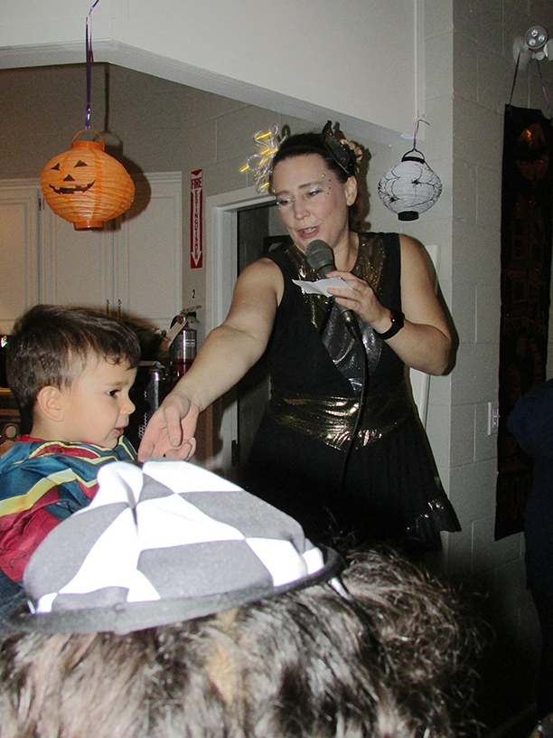 Woman in a Halloween costume with a microphone with a child in a costume