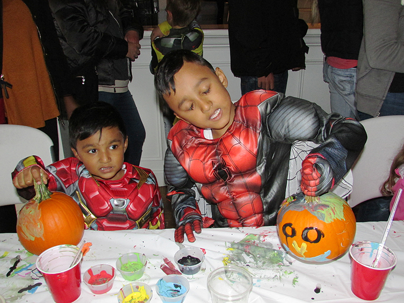 Two kids in Halloween costumes with decorated pumpkins