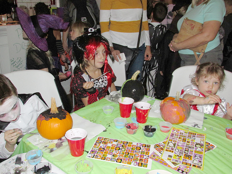 Three children in Halloween costumes decorating pumpkins