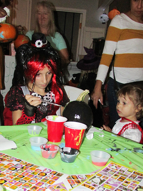 Two children in Halloween costumes decorating a pumpkin