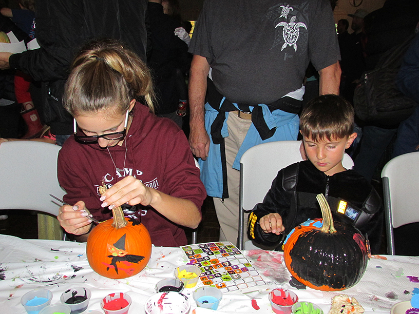 Adult and child in a Halloween costume decorating pumpkins