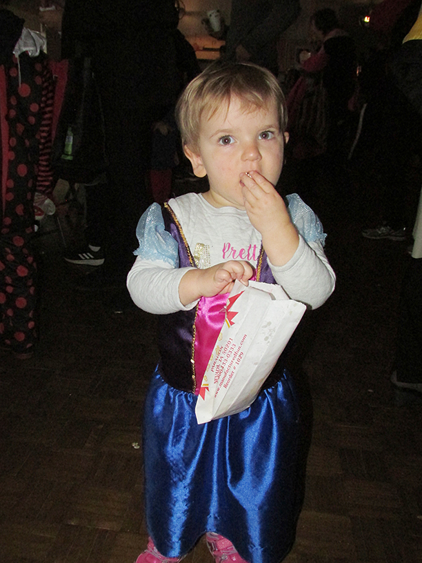 Child in Halloween costume eating popcorn
