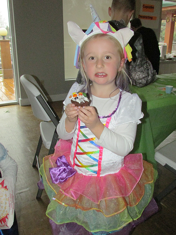 Child in Halloween costume eating a cupcake