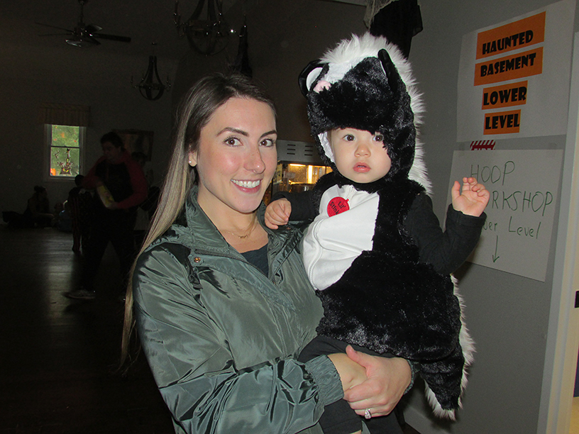 Woman holding a child wearing a skunk costume