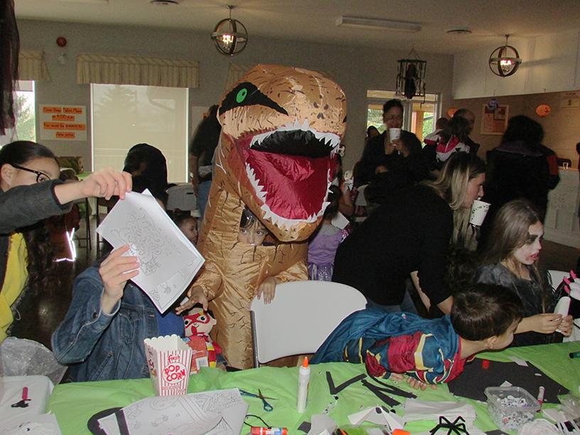 Children in Halloween costumes drawing
