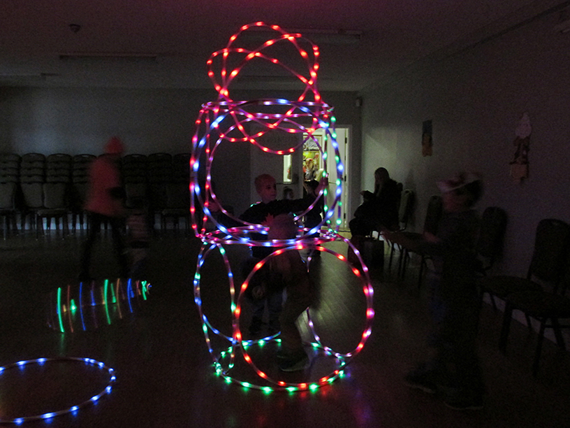 Child in structure made up of light up hula hoops