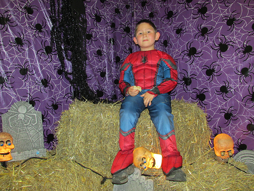 Child in Spiderman costume on a haystack