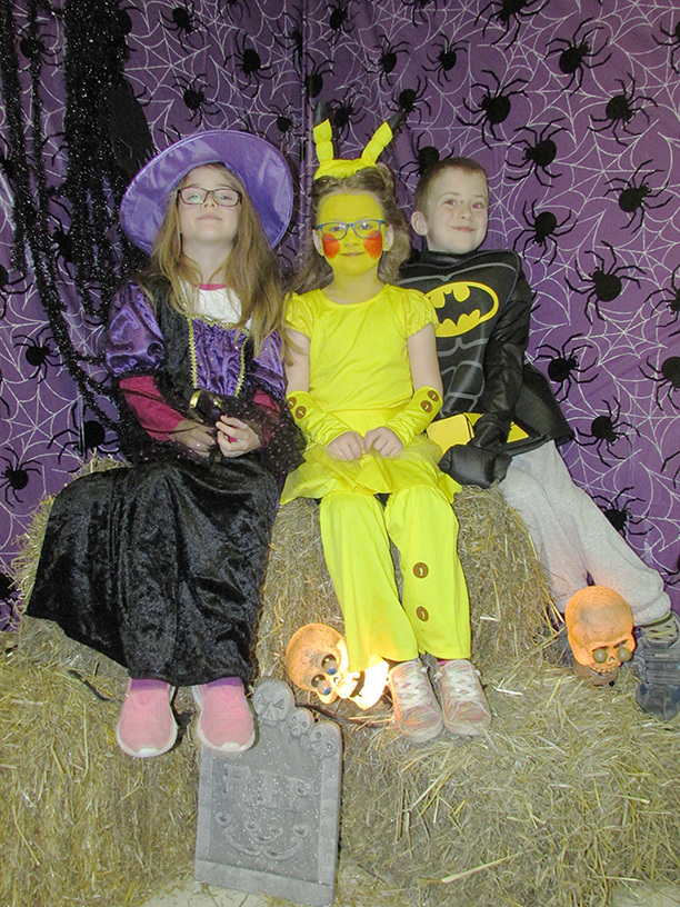 Children in costumes sitting on a haystack. There is a witch, Pikachu, and Batgirl