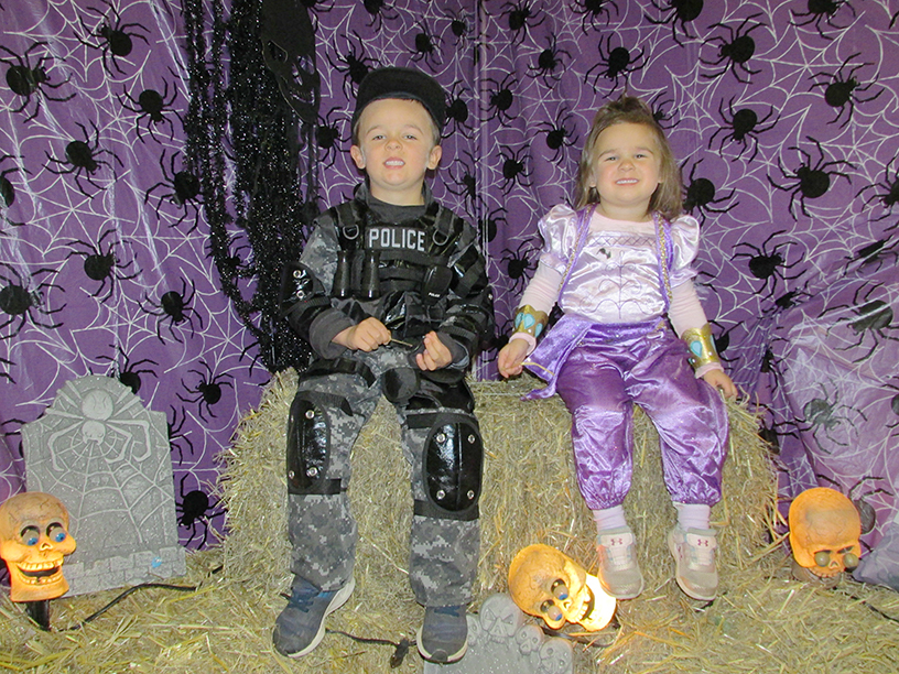 Children in Halloween costumes on a haystack. One is dressed as  police officer and one is dressed as a princess