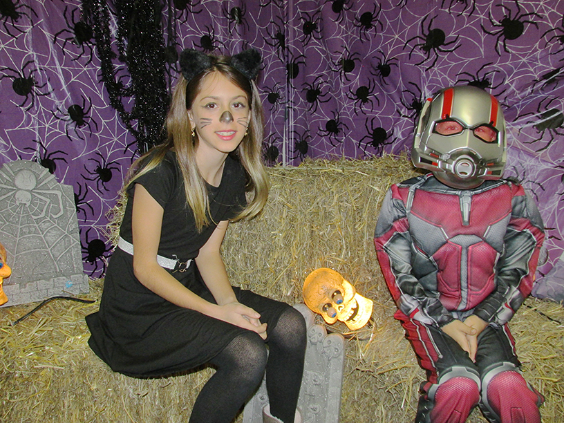 Two children dressed in Halloween costumes. One is dressed as a cat and the other is dressed as Antman