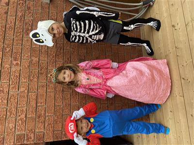 Children in Halloween costumes from Mario video games: Mario, Princess Peach, and Dry Bones
